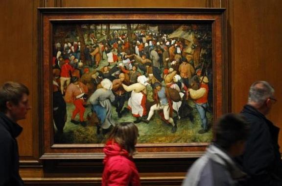 Visitors walking past 'The Wedding Dance' by Peter Breughel the Elder in the Detroit Institute of Arts