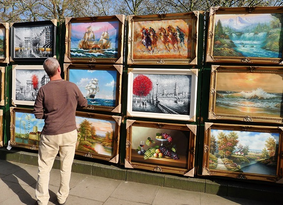The art market at entry level, paintings for sale on the railings in Green Park, London.